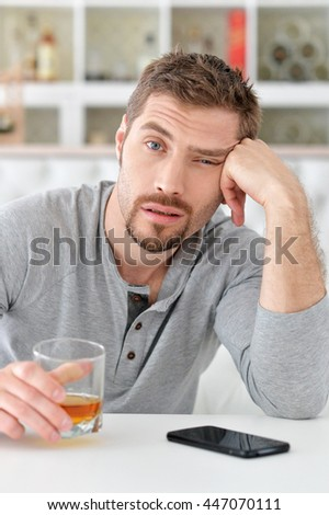 man with whiskey in glass