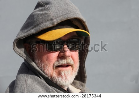Man with white beard wearing sunglasses, baseball cap, and hoodie with copy space - stock photo