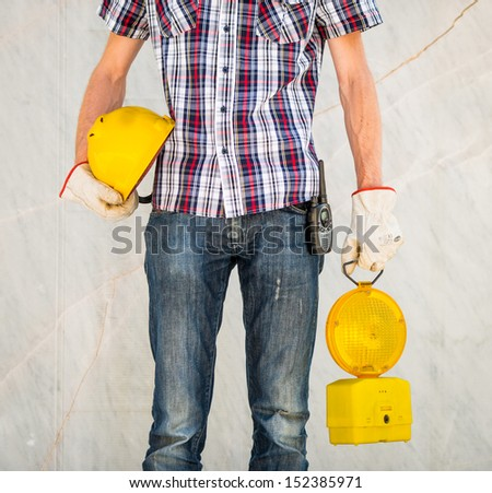 Man with white gloves and walkie talkie holding yellow helmet and flashing light - stock photo
