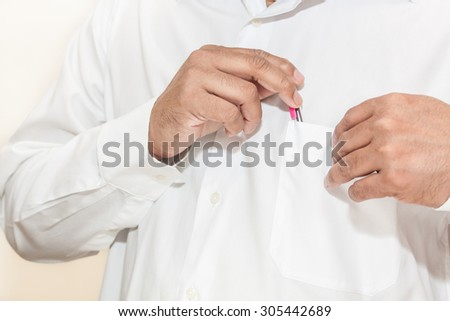Man with white long sleeve shirt taking pen from his pocket - stock photo
