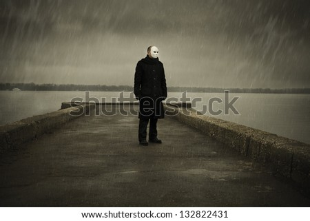man with white mask near the river and rainy day - stock photo