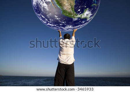 Man with white shirt holding the planet earth - science and environment concept - stock photo