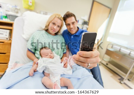 Man with woman and newborn babygirl taking selfportrait through cell phone in hospital room - stock photo