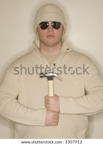 Man with wool hat, sunglasses, and wool sweater holds onto his hammer in front of his body in a sign of strength