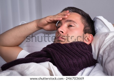 Man With Woolen Scarf Around His Neck Suffering From Cold And Fever - stock photo