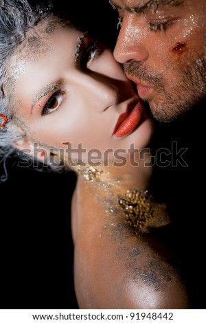Man with wounded face kissing woman on cheek - both covered with brocade