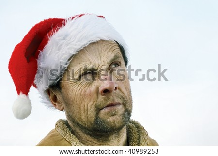 Man with wrinkly face skin in santa hat - stock photo