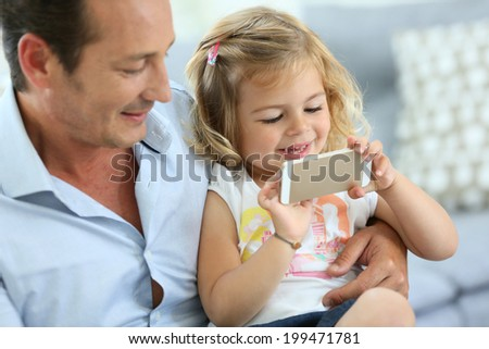 Man with 3-year-old girl playing with smartphone - stock photo