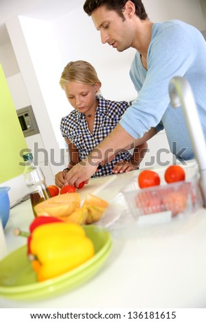 Man with young girl preparing meal in kitchen