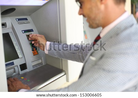 Man withdrawing money from ATM machine - stock photo
