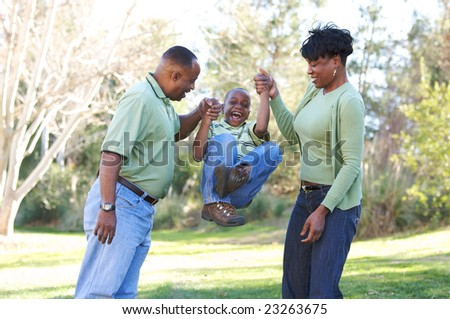 Man, Woman and Child having fun in the park. - stock photo