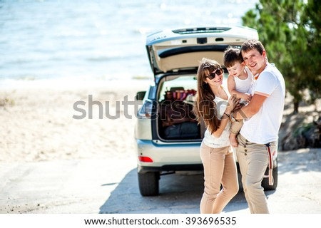 Man woman and child of three years old on the sea near the car of the jeep ready to travel - stock photo