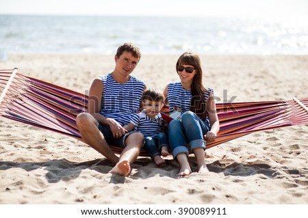 Man woman and child sitting in a hammock and relax on the beach