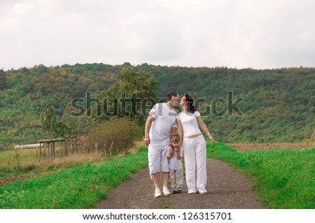 Man, woman and child walking along the road in a field. - stock photo