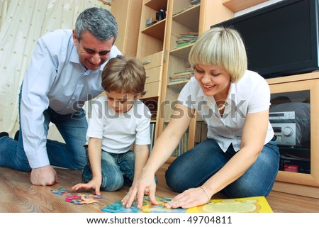 man, woman and little boy sitting on the floor in living room and reading book - stock photo