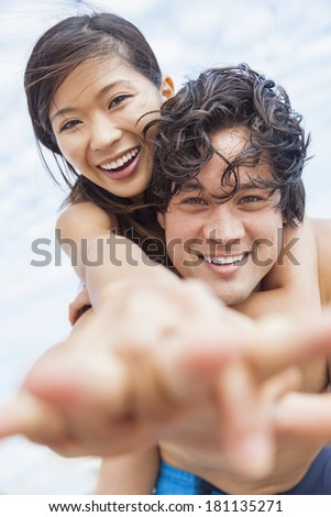 Man & woman Asian couple, boyfriend girlfriend in bikini, taking vacation selfie photograph at the beach  - stock photo