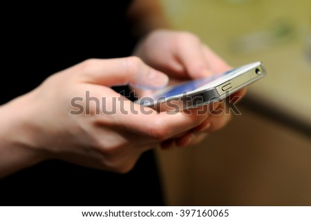Man woman holds phone in hands and typing by fingers chatting writing in social media , sms, email, notes, diary - stock photo
