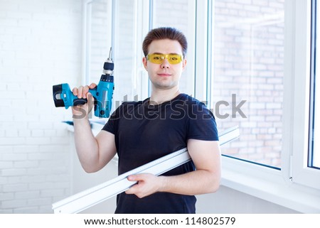Man worker after installing new windows. - stock photo