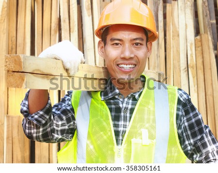 Man worker carpenter with helmet and safety vest carrying wood smiling look on your camera