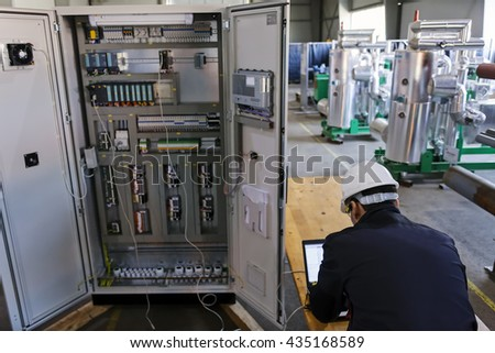 Man worker checking advanced industrial control panel in the production hall; note shallow depth of field
