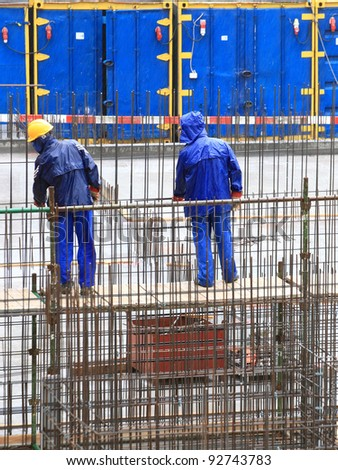 man worker construction building in rain - stock photo