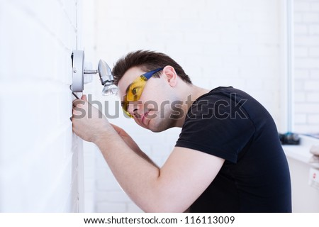 Man worker installing lamp on balcony. - stock photo