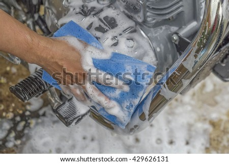 Man worker wash motorcycle.