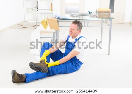 Man worker with ankle injury, concept of accident at work - stock photo