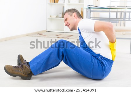Man worker with back injury, concept of accident at work - stock photo