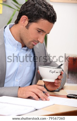 Man working and holding a cup