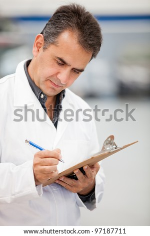 Man working as mechanic in a car garage and taking notes