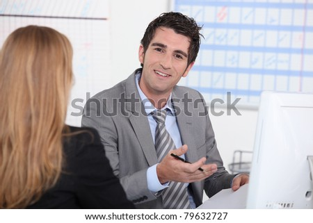 Man working at a computer with a customer - stock photo