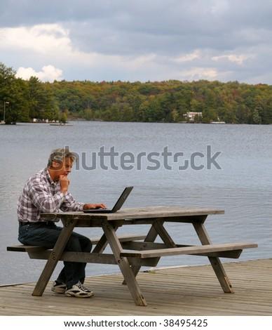 Man working at a lake - stock photo