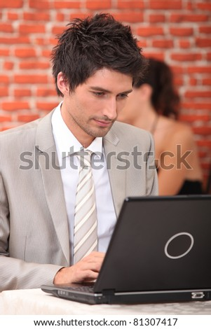 Man working at a laptop in a restaurant - stock photo