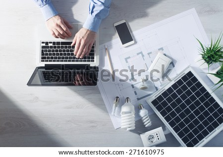 Man working at his desk on a laptop with energy saving CFL lamps, a solar panel and a house project, top view - stock photo
