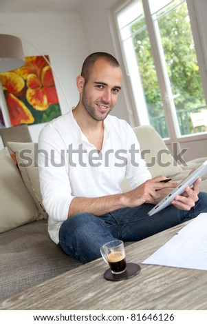 Man working at home with electronic tablet - stock photo
