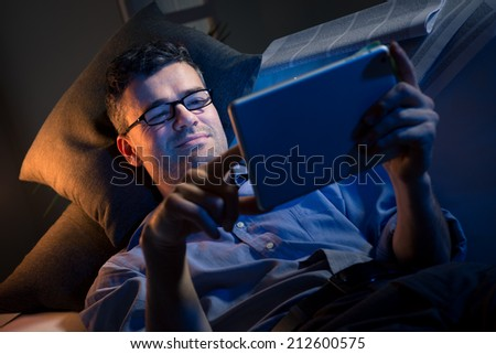 Man working at night lying down on sofa in the living room with tablet. - stock photo