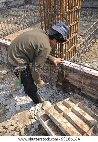 Man working at site construction. Photo Show is a template to place the concrete beam only. - stock photo