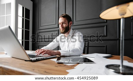 Man working at the office next to a window using a laptop