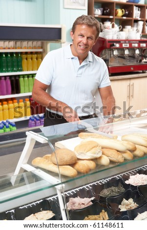Man Working Behind Counter In Cafe - stock photo