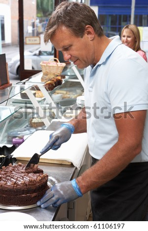 Man Working Behind Counter In Cafe Slicing Cake - stock photo