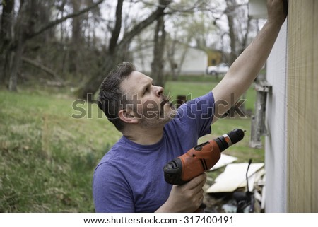Man working construction job holding drill with nails in his mouth - stock photo