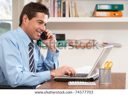 Man Working From Home Using Laptop On Phone - stock photo
