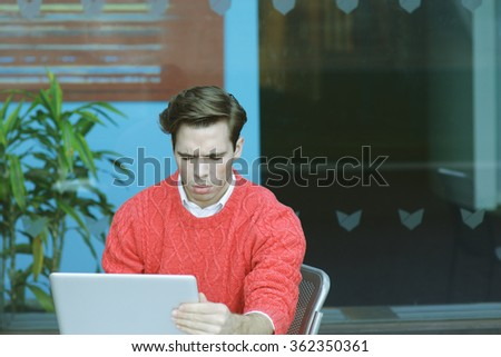 Man Working Hard in New York. Young blonde professional, wearing red knit sweater, sitting by glass wall outside office, reading, working on laptop computer, thinking. Technology in our daily life.  - stock photo