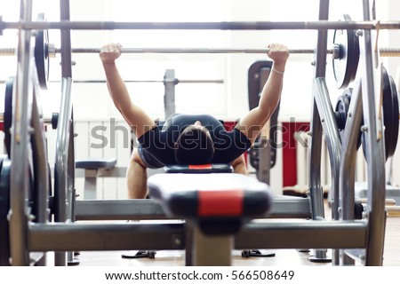 Man working his arms at the gym, He lifting the barbell and working his biceps, back view.