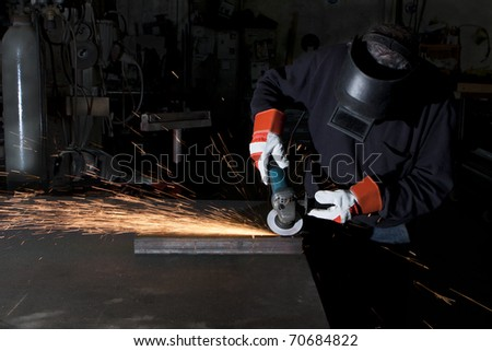 man working in a heavy industry workshop with a grinder sparks flaying all over