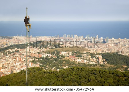 Man working in antenna with Barcelona city view in front of him - stock photo