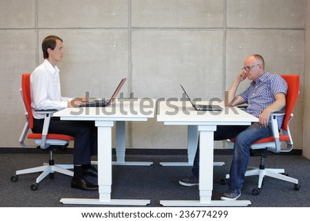 man working in correct sitting posture in office watching his colleague sitting in bad position at workstation - stock photo