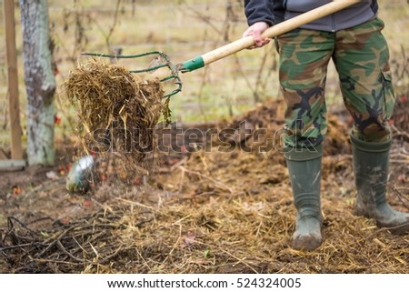 Man working in garden with fork. Fertilization of garden with ecological compost.