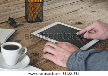 Man working in office using tablet computer. Male hand clicks on a blank screen tablet computer closeup. Copy space. Free space for text. Top view - stock photo